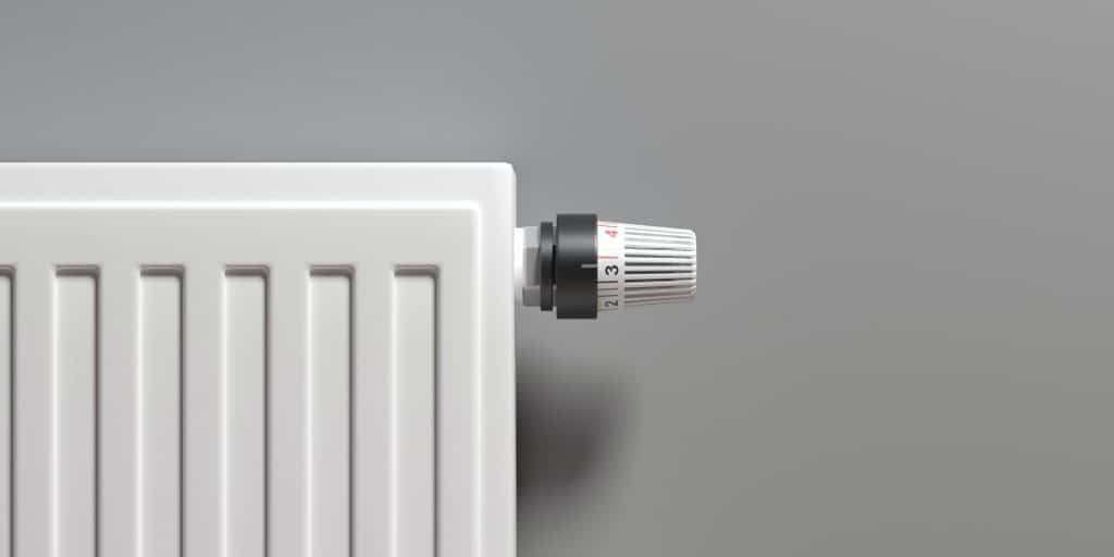 Radiator with thermostat, grey wall background. 3d illustration